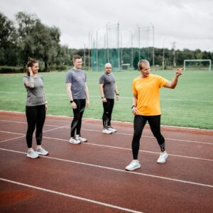 three people and coach on a running track