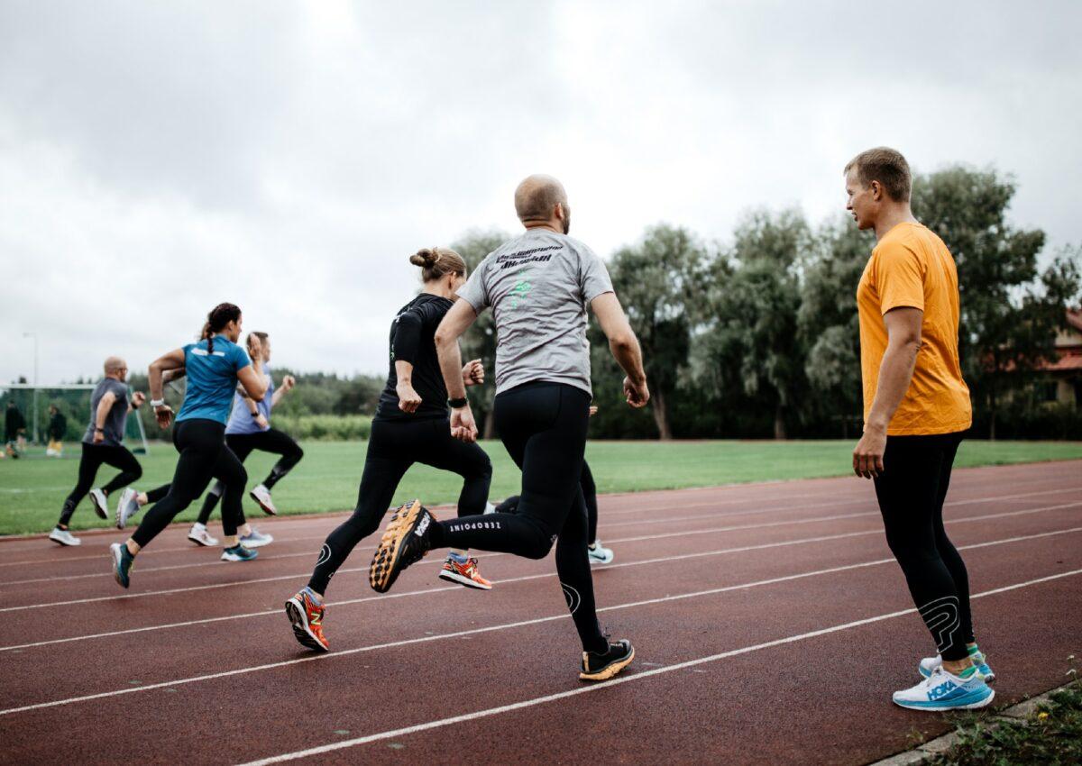 man coaching runners on a running track